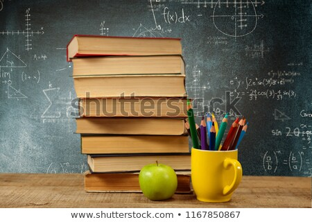 Stack of books by colored pencils in mug and apple on table against empty blackboard in school Stock photo © wavebreak_media