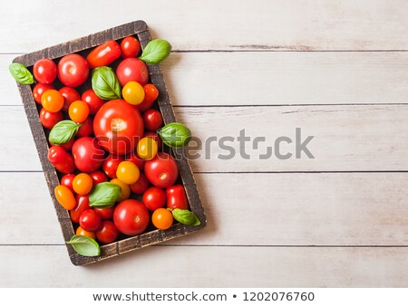 Organic Tomatoes with basil in vintage wooden board on wooden kitchen background. San Marzano, orang Stock photo © DenisMArt