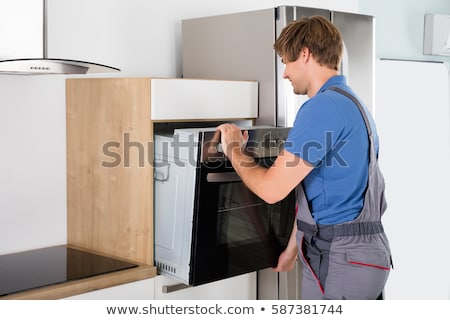 Technician In Overall Installing Oven Stock photo © AndreyPopov