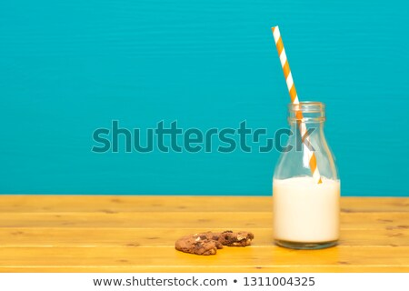 Straw and half full milk bottle with a half-eaten cookie Stock photo © sarahdoow