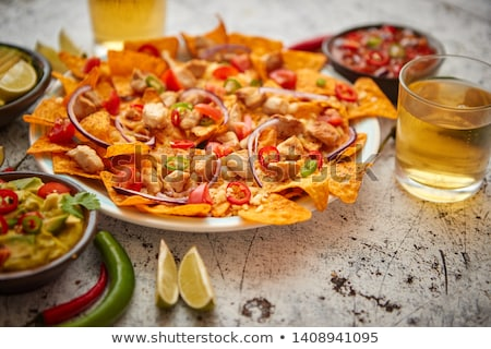 a plate of delicious tortilla nachos with melted cheese sauce grilled chicken stock photo © dash