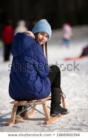 teenage girl sitting on sledge with flask and hot drink stock photo © monkey_business