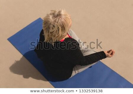 High angle view of senior woman meditating on a yoga mate on the beach  Stock photo © wavebreak_media