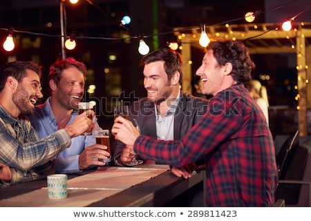 Four friends in a bar Stock photo © Kzenon