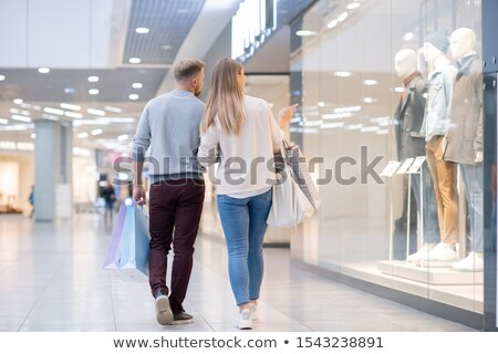 Back view of young shoppers paying attention to new male casualwear collection Stock photo © pressmaster