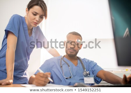 one of young clinicians showing his notes to colleague during discussion stock photo © pressmaster