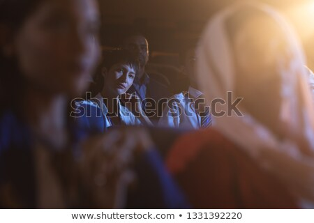 Front view of beautiful Asian businesswoman sitting and listening to the presentation with audience Stock photo © wavebreak_media