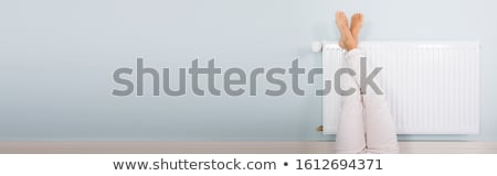 Young Woman Warming Up Her Feet On White Radiator Stock photo © AndreyPopov