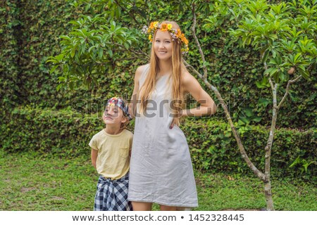 Boy tourist in sarong, national Balinese clothing and his mother with a wreath on his head Stock photo © galitskaya