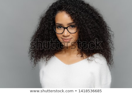 Close up shot of dark skinned female has satisfied expression, bushy curly hair, wears spectacles an Stock photo © vkstudio