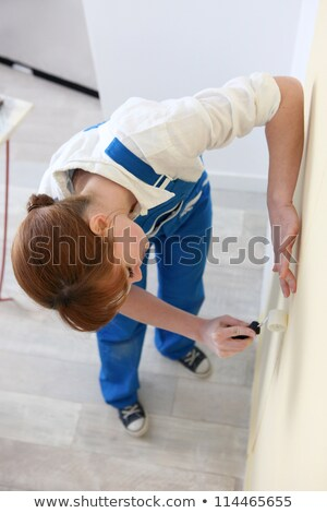 Woman smoothing a wallpaper seam Stock photo © photography33