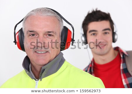 Builder with earmuff stood in front of teenager with headphones Stock photo © photography33
