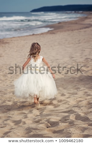 blonde in colorful dress on white sand stock photo © dolgachov