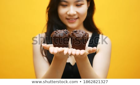 Delighted woman is eating a muffin Stock photo © wavebreak_media