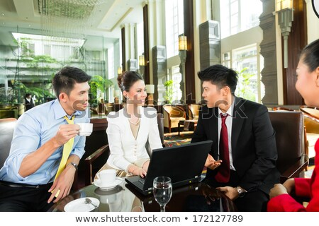 Asian business people at meeting in hotel lobby Stock photo © Kzenon