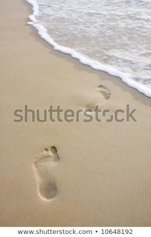 Voetafdrukken leidend zee menselijke weg hemel Stockfoto © avdveen