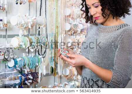 Young woman looking at trinket in shop Stock photo © Kzenon