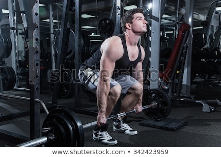 Young man is engaged in gym Stock photo © deandrobot
