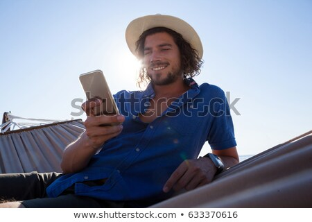smiling man using mobile phone while relaxing on hammock at beach stock photo © wavebreak_media
