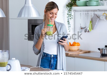 Pretty blonde woman holding her homemade smoothie Stock photo © wavebreak_media