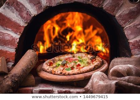 pizza baking in oven at pizzeria Stock photo © dolgachov