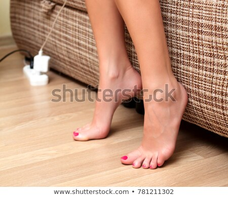 closeup shot of female feet on the wooden floor beside a bed stock photo © nobilior