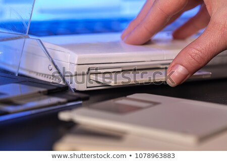 Hand inserting floppy diskette in old laptop computer - closeup Stock photo © lightkeeper
