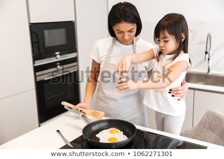 Morena mulher avental cozinhar ovos pequeno Foto stock © deandrobot