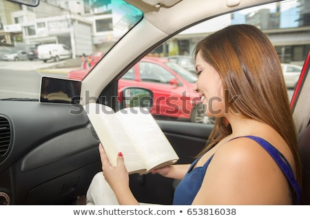 woman reading book while driving car stock photo © andreypopov