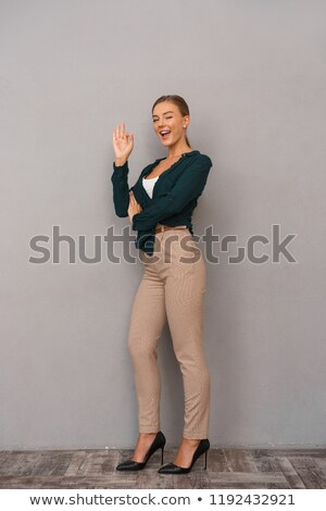 Beautiful business woman posing isolated over grey wall background showing okay gesture. Stock photo © deandrobot