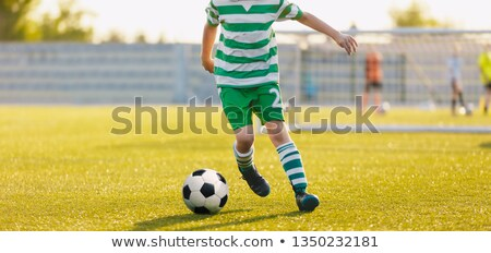 kid kicking soccer ball close up action of boy soccer player running after ball aged 8 10 playing stock photo © matimix