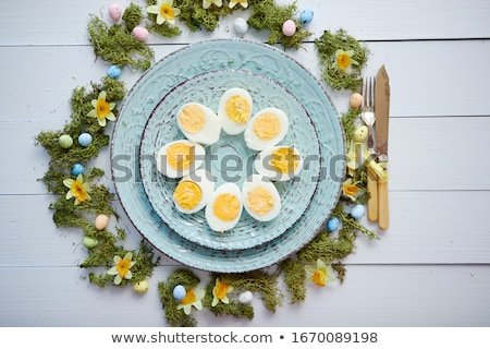 Easter table setting with flowers and eggs. Decorative plates with boiled eggs Stock photo © dash