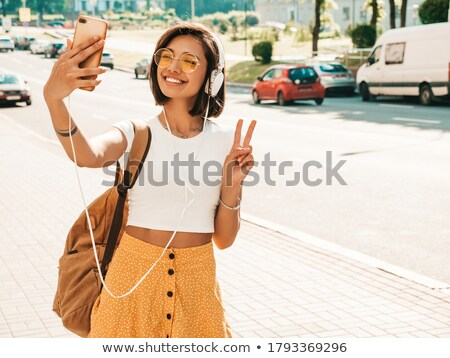 Happy young hipster woman making selfie on smartphone Stock photo © deandrobot