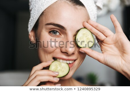 Photo of pleased woman with towel on head holding cucumber slice Stock photo © deandrobot