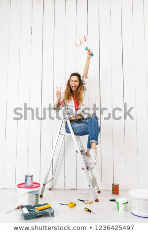 Full length photo of happy woman 20s sitting on ladder and paint Stock photo © deandrobot