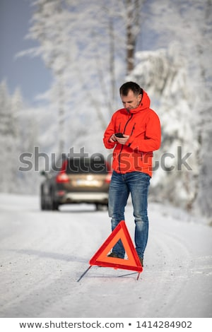 Handsome man setting up a warning triangle and calling for assisiance Stock photo © lightpoet
