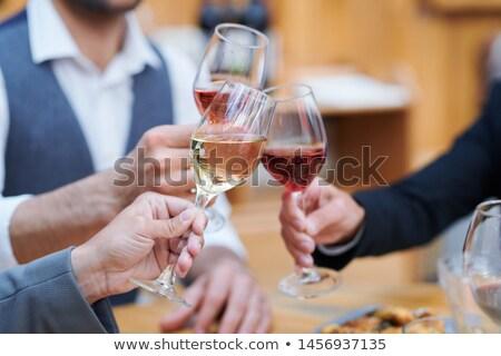 three humans clinking with wineglasses of varoius sorts of wine stock photo © pressmaster