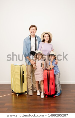 Happy young casual father, mother, son and daughter with baggage in studio Stock photo © pressmaster