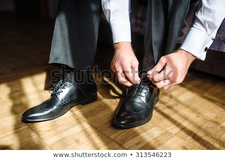 Business man tying shoe laces on the floor. Close-up Stock photo © ruslanshramko