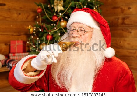 Santa Claus drinking champagne while celebrating Christmas in late December Stock photo © pressmaster