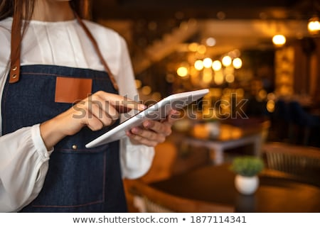 Young successful owner of modern restaurant or cafe holding touchpad Stock photo © pressmaster