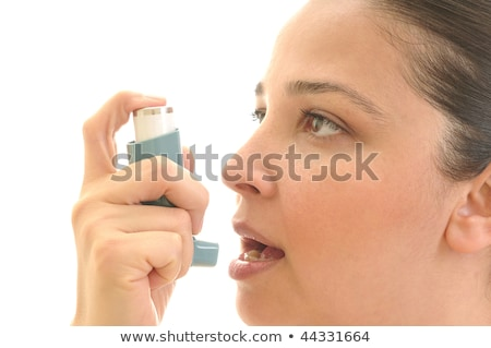 Stock photo: Close up image of a young woman using inhaler for asthma. White background studio picture