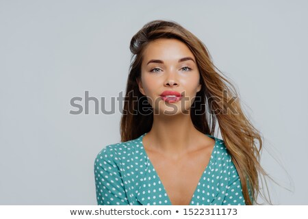 Portrait of pleasant looking young woman looks calmly at camera, has long hair, dressed in polka dot Stock photo © vkstudio