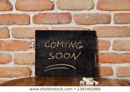 Black board with the phrase COMING SOON drown by hand on wooden  Stock photo © marylooo