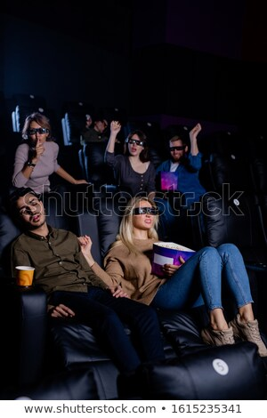 Group of friends and girlfriend trying to wake up tired guy napping in cinema Stock photo © pressmaster