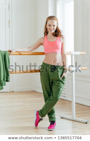 Self confident cheerful redhead woman dancer stands near ballet barre, wears sporty top and trousers Stock photo © vkstudio