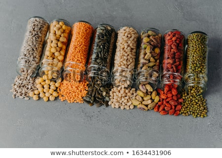 Nutitious grains spilled from glass bottles on grey texture background. Jars with different kinds of Stock photo © vkstudio
