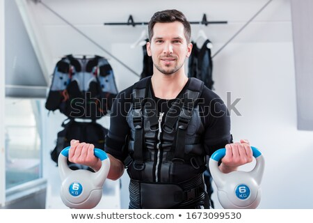 Strong man in ems gym doing fitness training with weights Stock photo © Kzenon