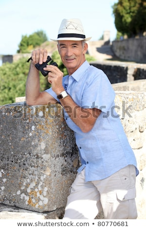 Senior man at a citadel with a pair of binoculars Stock photo © photography33