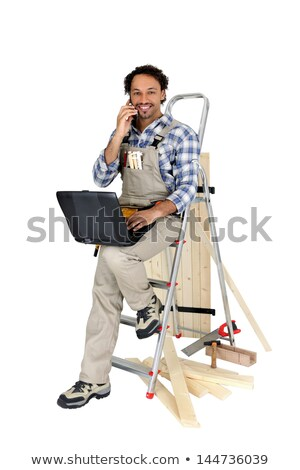 carpenter perched on ladder whilst making a telephone call stock photo © photography33